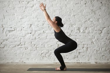 woman practicing Bikram yoga in a studio in front of white brick wall wearing black jumpsuit