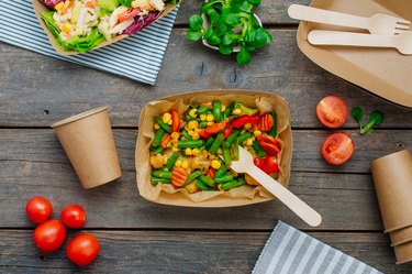 Steamed vegetables in the brown kraft paper food containers on wooden background