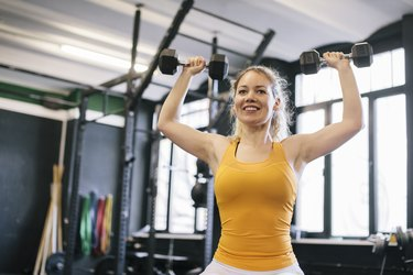 Young Woman Doing Dumbbell Exercises in Gym