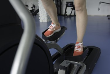 Woman's feet on cross-trainer at gym