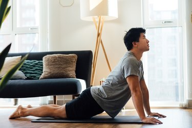 man practicing upward facing dog and stretching in his living room