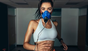 Sportswoman with mask running on treadmill in gym