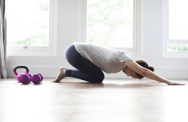 Woman warming up in child's pose for at-home crossfit 21-15-9 workout