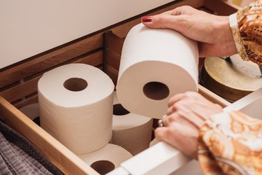 A woman reaching for a roll of toilet paper stored in a bathroom drawer