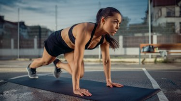 Beautiful Energetic Fitness Girl Doing Mountain Climber Exercises. She is Doing a Workout in a Fenced Outdoor Basketball Court. Evening After Rain in a Residential Neighborhood Area.