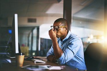 A stressed man sitting at his desk at work and rubbing his eyes