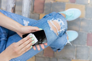 Female hands wiping the touch screen phone with antibacterial wipes
