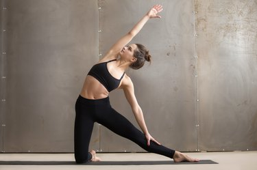 Young attractive woman stretching in Parighasana pose, grey stud