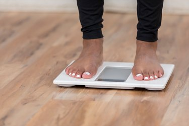 An unrecognizable woman checks her weight to calculate her BMI