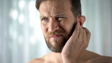 A man touching his ear because he has a bad smell behind his ears