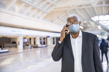 man on phone at the airport wearing face mask traveling by plane during COVID pandemic