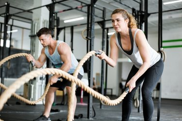 Fitness people working out with battle ropes