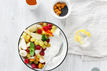 Top view full fruit breakfast and natural yoghurt bowl