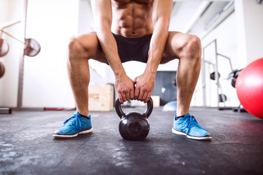 Unrecognizable fit hispanic man in gym working out with kettlebell