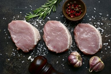 Slices of raw organic pork meat with ingredient for making