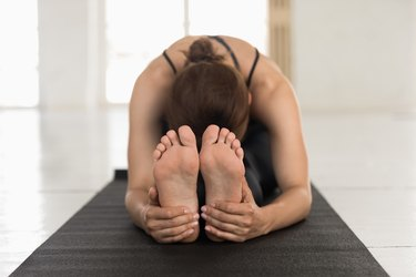 Young woman practicing yoga, Seated forward bend, paschimottanasana