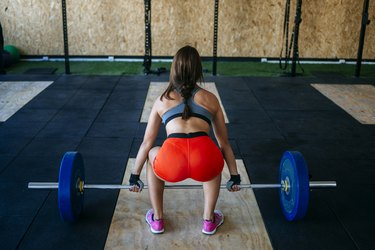 Back view of woman preapring to lift barbell in gym