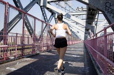 Young active woman running on Williamsburg Bridge