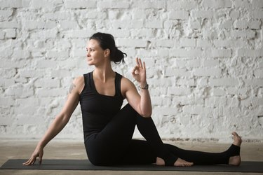 Young yogi attractive woman in Ardha Matsyendrasana pose, white loft