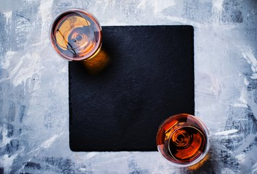Cognac in two glasses on stone background, top view