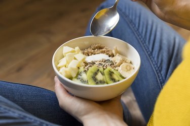 An unrecognizable woman eating a healthy breakfast bowl filled with yogurt, buckwheat, seeds and fresh fruits