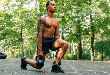 Man exercising with kettlebell outdoors. Athlete doing squats using kettlebells.