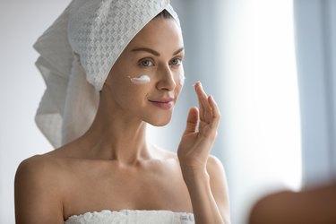 Close up beautiful woman applying cream, looking in mirror