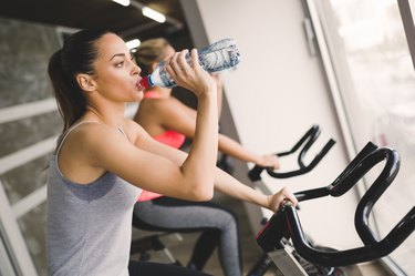 Sporty women cycling in gym during fitness class