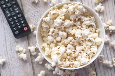 remote control and popcorn in a bowl