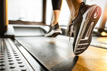 Close up of unrecognizable athlete running on a treadmill in a gym.