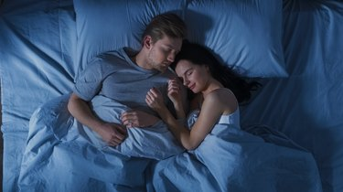 Happy Young Couple Cuddling Together in Bed