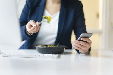 Counting calories Businesswoman eating lunch in office