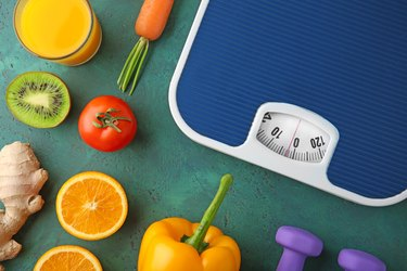 Fresh fruits and vegetables, which don't have a SmartPoints value, surrounding a scale.