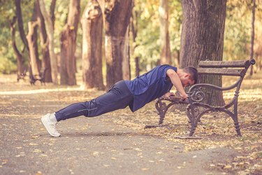 Young sporty man doing push-ups outdoors for chest muscles