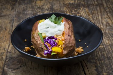 Sweet potato Kumpir withbell pepper, red cabbage, couscous, yoghurt sauce and parsley