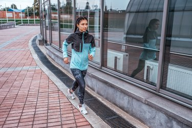 Woman athlete girl runs in the city in autumn in spring, fitness workout, motivation is power. Active lifestyle. Sportswear, free space, achievement, success, endurance competition.