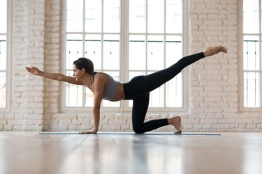 Young sporty attractive woman practicing yoga, doing Donkey Kick exercise