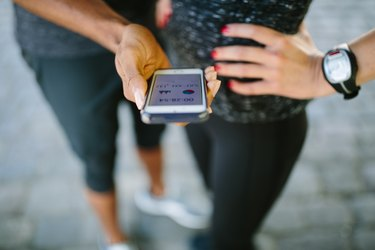 Young people checking their fitness progress on smartphone