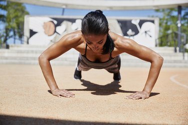 Fit woman doing pushups outdoors