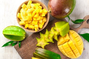 Composition with fresh mango and starfruit on wooden background