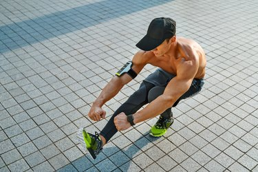 man wearing leggings hat and arm band doing squat on one leg