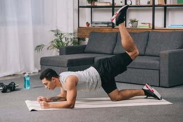handsome mixed race athlete with tattoo on hand doing exercise on legs on fitness mat in living room