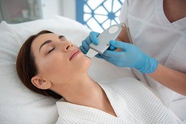 Lady enjoying of suprasonic procedure of face