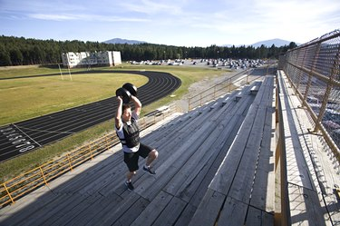 man in shorts running stairs with weighted vest and weight held above head