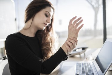 Woman working with computer and having wrist pain