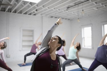 Focused woman practicing yoga reverse warrior pose in yoga class