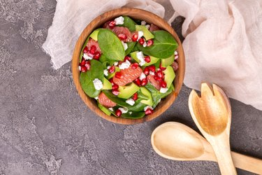Tasty salad with grapefruit, spinach, feta, avocado and pomegranate in wooden bowl