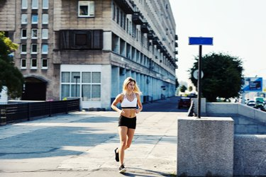 Young woman running on city street