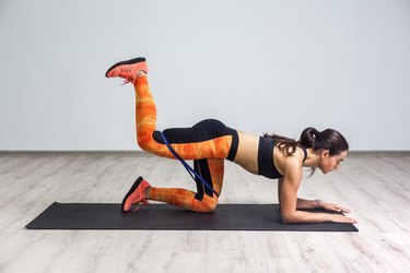 Side view portrait of strong and fit athletic young woman in sportswear with bands training legs and glutes muscular. Fitness exercising with expander.