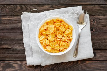 Tasty corn flakes in bowl. Rustic wooden background.